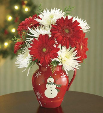 red daisies and spider mums in red ceramic vase