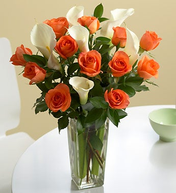 orange roses and white callas in a vase